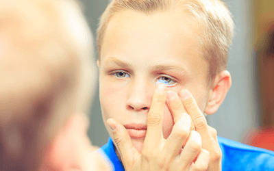 child putting in contact lens